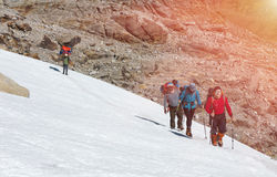 Group of Climbers walking on Snow Nepalese Porter shining Sun. Group of Climbers with Backpacks and climbing Gear in protective windproof Clothing walking on Stock Photo