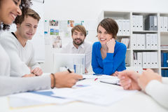 Group of co-workers having a brainstorming session. Sitting around a table together in the office as they plan their business strategy Stock Photos