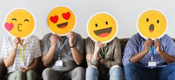 Group of co-workers holding emoticons. On their faces stock photo