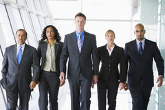 Group of co-workers walking in office space. To camera royalty free stock photography