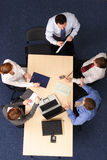 Group coaching. Businesspeople gathered around a table for a meeting, brainstorming. Aerial shot taken from directly above the table royalty free stock image