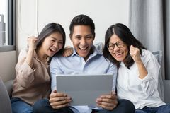 Group of colleague. Looking at digital tablet with happiness Stock Image