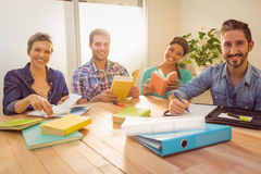 Group of colleagues reading books and smiling at camera. In the office royalty free stock photography