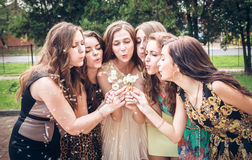 Group of College Girls Blowing Dandelion Seeds Stock Images
