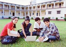 Group of college students. Group of Indian / Asian college students studying over the grass in the campus Royalty Free Stock Photo