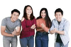 Group of college students applauding on studio. Group of college students looks happy while applauding at the camera, isolated on white background stock images