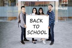 Students holding a white board saying back to school Stock Image