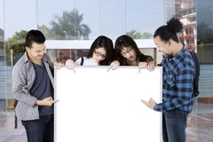 Group of college students pointing on white board with copy space. In front of university entrance Royalty Free Stock Images