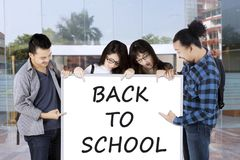 Students pointing on whiteboard saying back to school. Group of college students pointing on white board saying back to school Royalty Free Stock Images