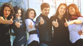 Group of college students smiling friendly standing next to each other with arms extended forward and the thumbs up. A group of college students smiling friendly Stock Photos