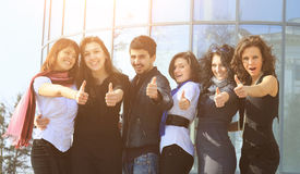 Group of college students smiling friendly standing next to each other with arms extended forward and the thumbs up Stock Photo