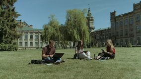 Group of college students studying on campus lawn. Group of diverse college students studying with digital devices while sitting on campus lawn over historical stock video
