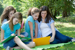 Group of college students studying together. Group of attractive young female college students studying together sitting on a rug in the garden in the shade of a Stock Photos