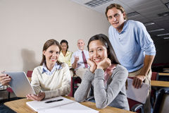 Group of college students and teacher in class. Multiracial group of college students and teacher in class royalty free stock photos