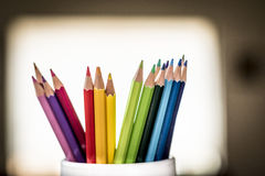A group of color pencils in a white cup Stock Photos