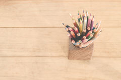 Group of color pencils in a wood cup . Stock Photos
