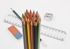 Group of colored pencils with school supplies. Group of colored pencils with basic school supplies on a white background stock images