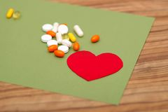 A group of colored pills and a red heart on a green background on the table. royalty free stock image
