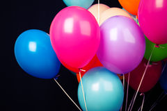 Group of colorful balloons on ribbons on black Royalty Free Stock Photos