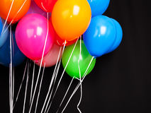 Group of colorful balloons on ribbons over black Stock Image