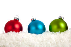 A group of colorful Christmas Baubles on White. A group of colorful Christmas Baubles on a white background with copy space and fake snow Stock Photo