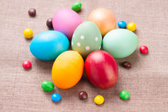 Group of colorful Easter eggs and colored candies. Several colorful Easter eggs lying on linen fabric cloth close up Stock Photo