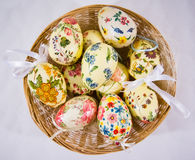 Group of colorful easter eggs decorated with flowers made by decoupage technique, in a basket Royalty Free Stock Photos