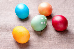 Group of colorful Easter eggs lying on linen. Several colorful Easter eggs lying on linen fabric cloth close up Royalty Free Stock Photography
