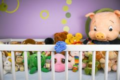 Group of colorful fluffy stuffed animal toys closeup with hanging blue small baby shoe royalty free stock images