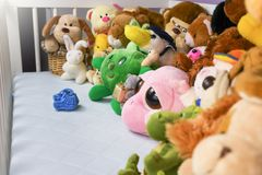 Group of colorful fluffy stuffed animal toys closeup with hanging red small baby shoe royalty free stock image