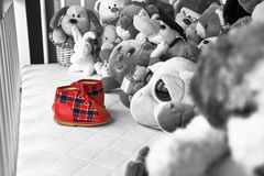 Group of colorful fluffy stuffed animal toys closeup with hanging red small baby shoe. Group of colorful fluffy stuffed animal toys close up looking at red small stock photo