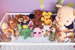 Group of colorful fluffy stuffed animal toys close up in a white wooden baby crib. Waiting for newborn baby to arrive home royalty free stock image