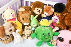 Group of colorful fluffy stuffed animal toys close up in a white wooden baby crib. Waiting for newborn baby to arrive home stock photography