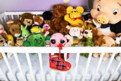 Group of colorful fluffy stuffed animal toys closeup with hanging red small baby shoe. On a white crib fence stock image