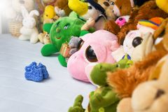 Group of colorful fluffy stuffed animal toys closeup with hanging red small baby shoe. Group of colorful fluffy stuffed animal toys close up looking at blue stock image