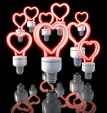 Group of colorful fluorescent lamps, heart shaped, red glow, 3d rendering on dark background. 3d rendering on black, dark background over reflecting surface Royalty Free Stock Photo