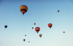 Group of colorful hot air balloons against a blue sky Stock Photos