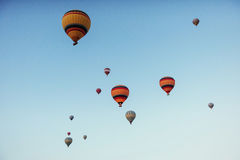 Group of colorful hot air balloons against a blue sky. A group of colorful hot air balloons against a blue sky Royalty Free Stock Images