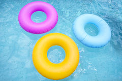 Group of colorful inflatable tubes floating in a swimming pool Royalty Free Stock Image