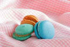 Group of colorful macaroons on pink cloth. Stock Photo