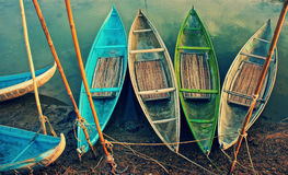 Group of colorful rowing boat, abstract curve. Group of colorful rowing boat anchor on day, abstract curve of bamboo boat in vintage colors, stakes on mud Royalty Free Stock Photos