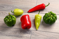 Group of colorful sweet peppers on a wooden table Stock Images