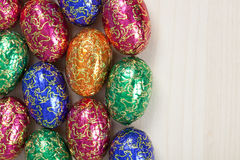 Group of colourful easter eggs. A group of colourful easter eggs all to the left of the photo, showing the wood background on the right Royalty Free Stock Photo