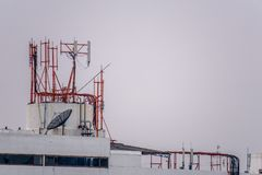 Group of communication posts with so many frequency radio antennas and TV satellite dish on the roof top of the tall building. Stock Photography
