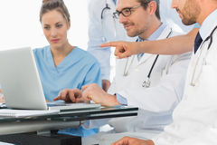 Group of concentrated doctors using laptop together Stock Images