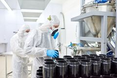 Working Process in Sport Nutrition Factory. Group of concentrated factory workers wearing coveralls, respirators and rubber gloves filling in plastic bottles Royalty Free Stock Photos