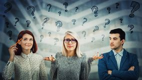 Confused group. Group of confused young people thinking with interrogation marks above head. Have the same common question, sharing thoughts together. Employee royalty free stock photography