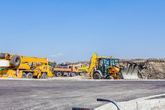 The group of construction machinery is parked at building site Stock Photos