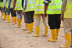 Group of construction workers assemble at the open space. Royalty Free Stock Images