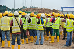 Group of construction workers assemble at the open space. Royalty Free Stock Photo